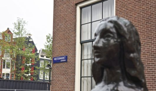 Statue honoring Anne Frank in front of her famous home in Amsterdam